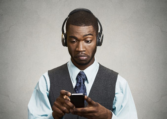 Corporate executive with headphones holding mobile phone