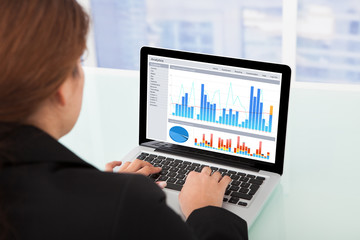Businesswoman Watching Financial Charts On Laptop