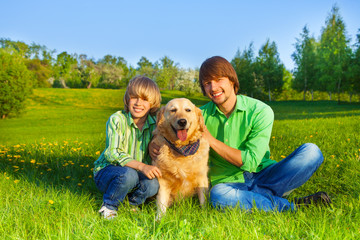 Happy kid, father and dog sit in park on grass