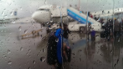 Rainy airport view from window with drops