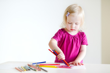 Cute toddler girl drawing with colorful pencils