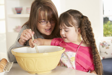 Girl with Downs Syndrome baking with mother