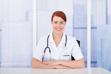 Beautiful Young Female Doctor Sitting At Desk