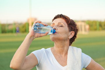 attractive woman 50 years in a white shirt drinks water from a b