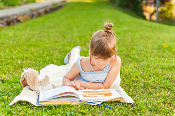 Portrait of adorable little girl resting outdoors