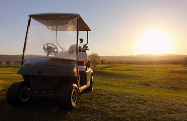 Golf cart over nice green and sunset