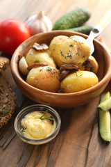 Young boiled potatoes in bowl on wooden table, close up
