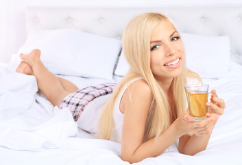 Young beautiful woman with cup of tea in bed