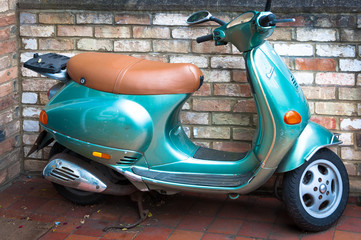 Vintage scooter parked next to a brick wall