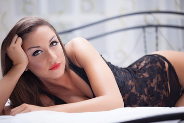 sexy woman in black lingerie lying on a bed