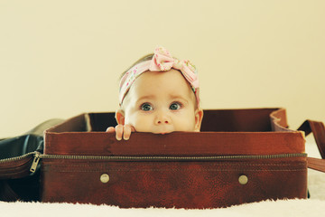 Portrait of aborable baby lying in vintage bag