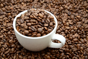 cup with coffee grains on a coffee beans background