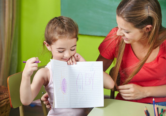 Girl showing drawing to nursery teacher in kindergarten