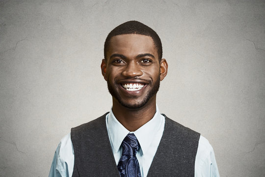 Portrait happy, smiling corporate executive grey wall background