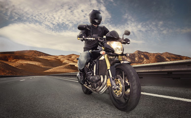 Fototapete - Man seat on the motorcycle on the desert road