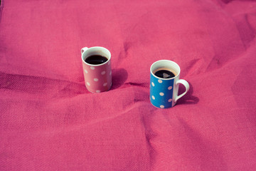 Two cups on a pink blanket