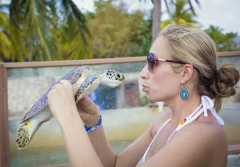 Beautiful woman kissing a young sea turtle while on vacation