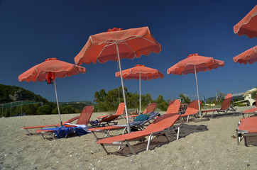 Fototapete - orange umbrellas - karavostasi beach parga greece