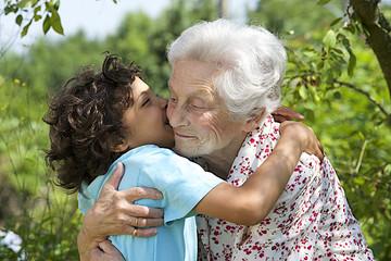 portrait d'un petit garçon embrassant sa grand mère