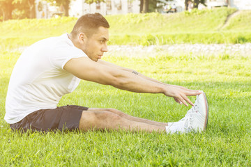 Fit male exercising sit up outside in grass in summer