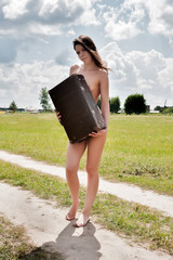 Pretty nude woman covering her body by suitcase