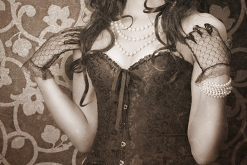 woman wearing black corset and pearls against retro background