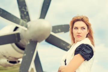 beautiful woman posing against plane