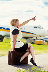 beautiful woman sitting on old suitcase against plane