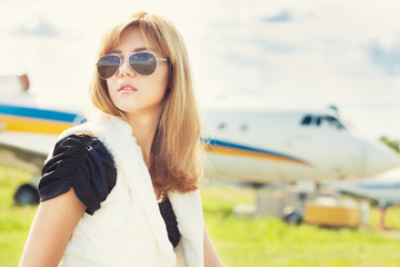 beautiful woman wearing sunglasses against plane