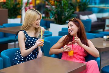two woman friends drinking juice in bar
