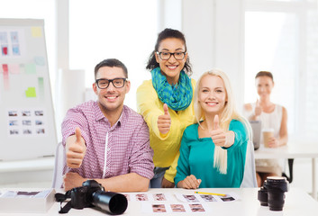 smiling team with printed photos working in office