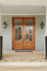 Twin wooden doors to a green family home