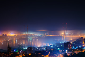 Vladivostok cityscape night view. Fog over the city.