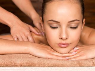 Beautiful young woman relaxing in the spa salon.