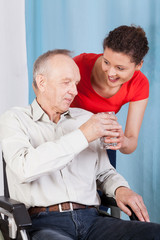Nurse giving disabled man glass of water