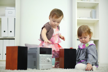 Two little cute girls play with music system in room at home