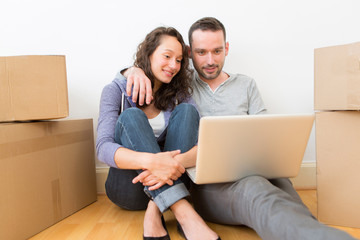 Young couple using laptop while moving in new flat