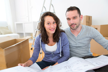 Young couple watching plans in their new flat