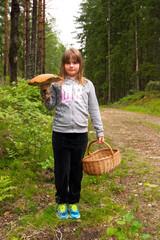 Cute girl picking big mushrooms in Swedish forest