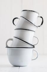five white enameled mugs