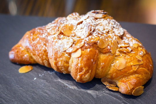 Fresh croissant with almonds on the plate
