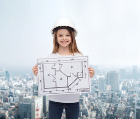 smiling little girl in helmet showing blueprint