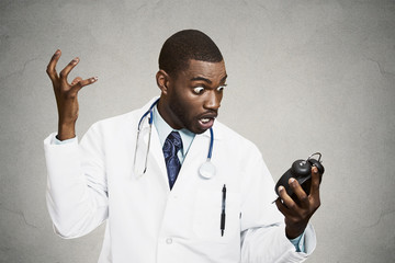 Stressed doctor, holding alarm clock, grey wall background