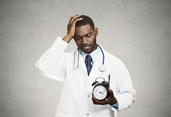 Stressed doctor holding alarm clock, grey wall background