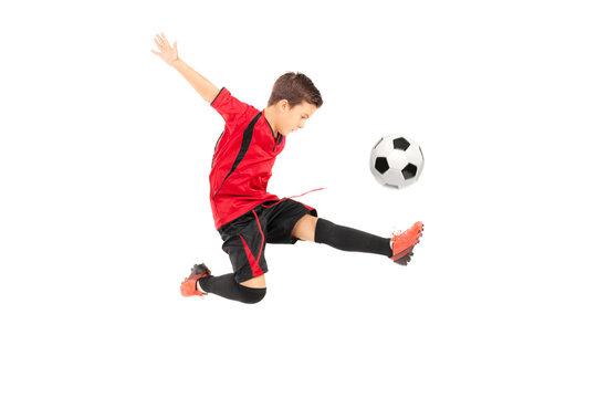 Junior football player kicking a ball