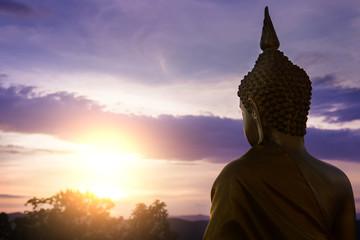 The back of Buddha image and sunset