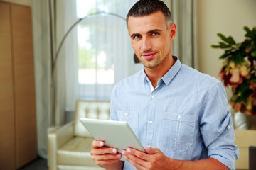 Smiling man standing with tablet computer at home