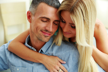 Couple hugging with eyes closed at home