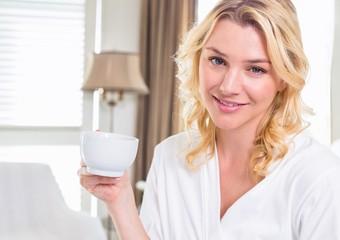 Pretty blonde in bathrobe drinking coffee smiling at camera