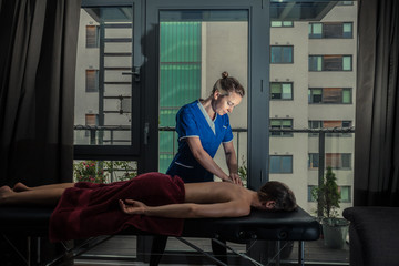 Massage therapist treating patient at home